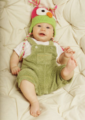 Portrait of cute happy 5 month old baby boy with funny hat.