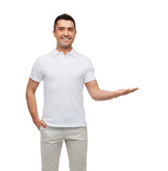 smiling man showing something on empty palm