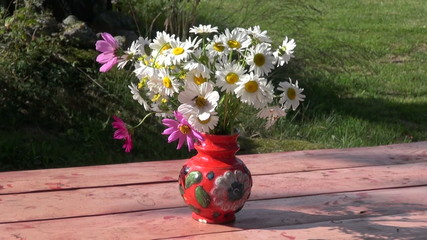 red vase with flowers on table in summer farm