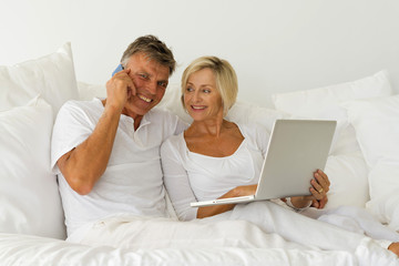 Senior couple surfing the web on sofa