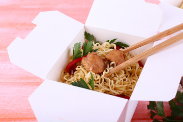 Chinese noodles with meat and pepper in takeaway box