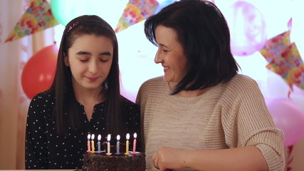 Mother and daughter celebrating with birthday cake