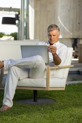 Senior man sitting with laptop