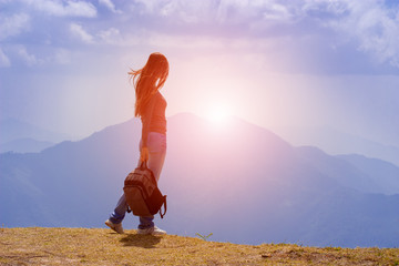 Woman Traveler with Backpack looking at mountain landscape