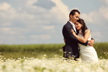 Bride and Groom posing in the fields