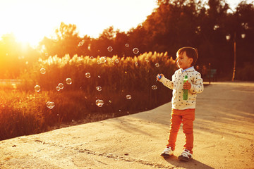 Little boy playing with soap bubbles