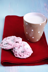 Pink cookies and cup with milk on table close-up
