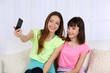 Two girls sitting on sofa and making photo on mobile phone