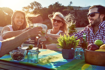 cheerful friends drinking cocktails