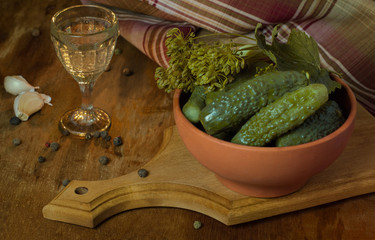 Pickles in a clay bowl and glass of vodka