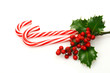 christmas candy canes with a branch of holly - 78644187