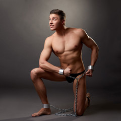 Sexy bodybuilder posing in handcuffs