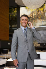 Businessman phoning in a living room