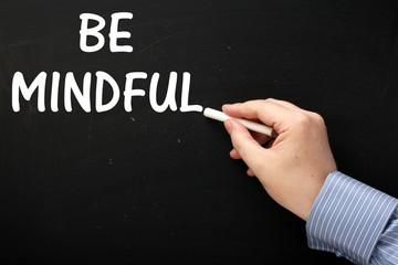 Writing the phrase Be Mindful on a blackboard