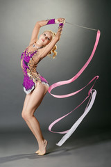 Studio shot of curved gymnast dancing with ribbon