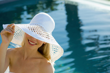 Young girl with hat by the pool