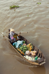 Woman on boat in conical hat floating down Mekong, Can Tho