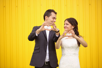 Bride and Groom doing love sign with their hands