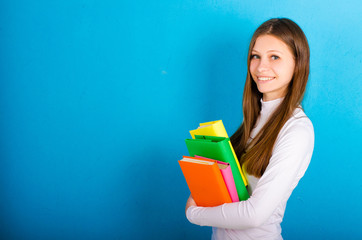 girl with colored books on a blue background
