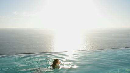 Woman swimming in luxury swimming pool