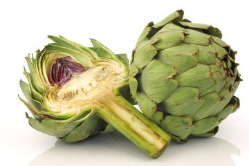 one whole and cut artichoke on a white background