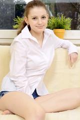 Teen in Bluse und Hot Pants entspannt auf Sofa