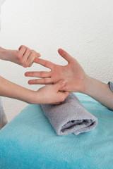 A man in a nail salon receiving a manicure