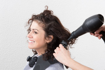 Woman at the hairdresser blow drying her hair