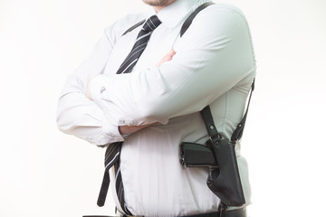 pistol in a holster under his arm a man on white background