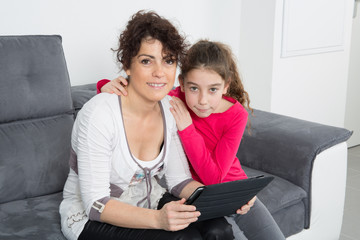 bright picture of hugging mother and daughter looking at tablet