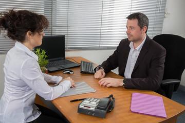 Handsome businessman interviewing female