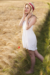 Cheerful beautiful young blonde girl in white dress with straw h