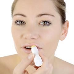 Frau mit Pflegestift für Lippen und Mund