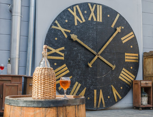 Bottle and glass of wine on a barrel of the clock