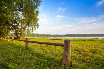 Wooden fence on lake coast, Russian landscape