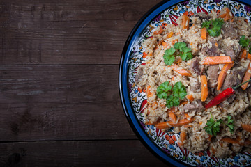 Delicious pilaf on a turkish plate on old wooden table. Rustic s