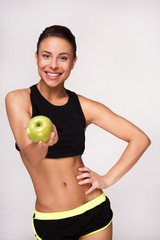 Sporty mixed race woman showing an apple to camera