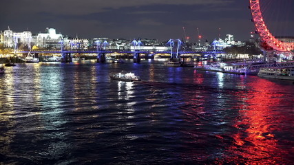 Nighttime Thames from Westminster bridge with reflected lights.