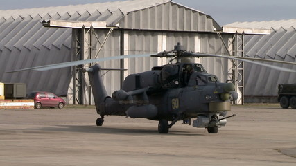 Military helicopter on background of hangars