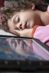 female child sleeping next to tablet