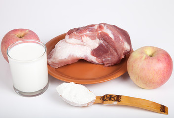 Raw meat, apples, flour and a glass of milk. Still life on white