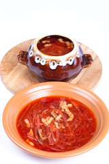Russian borscht soup in a bowl and a pot on a light background