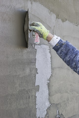 Worker's hand plastering a exterior wall 2