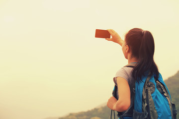 woman hiker on mountain taking photo with smart phone