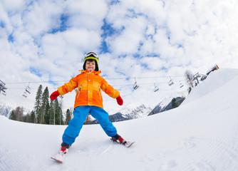 Boy with mask and helmet skiing on ski resort