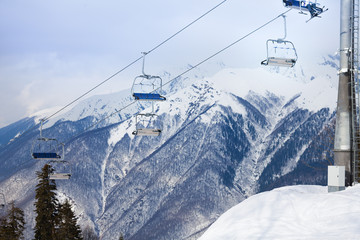 Mountain ski chair lift ropeway and snowy peaks
