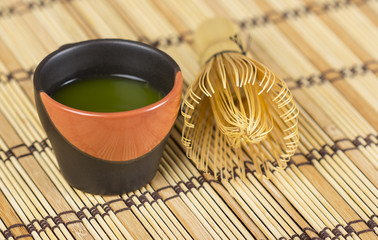 Green matcha in cup with bamboo whisk