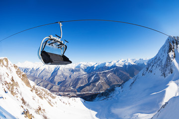 Chair on ski lift over mountain peaks panorama