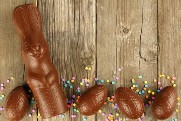 Chocolate Easter eggs and bunny border on wood