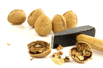 a cracked and some whole  walnuts with a hammer